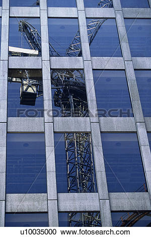 Stock Photography of Tower crane reflected in glass facade of.