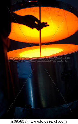 Stock Photo of Silhouette of man using furnace in glass factory.