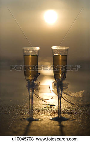 Pictures of Pair of flute glasses filled with champagne with bows.