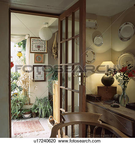 Stock Photography of Lighted lamp on table beside open glazed door.