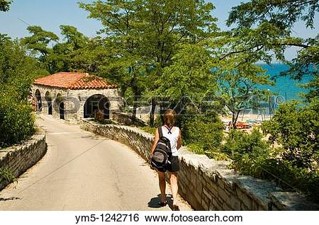 Stock Images of Woman walking down driveway to Glencoe Park beach.