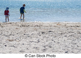 Stock Photography of Two Kids Playing on the Beach as the Sun is.