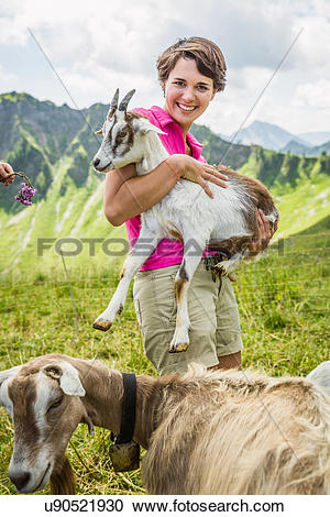 Stock Photography of Young woman holding kid goat, Tyrol, Austria.