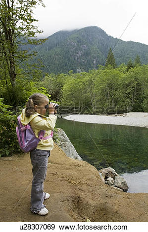 Stock Photograph of Little girl looking through binoculars on a.