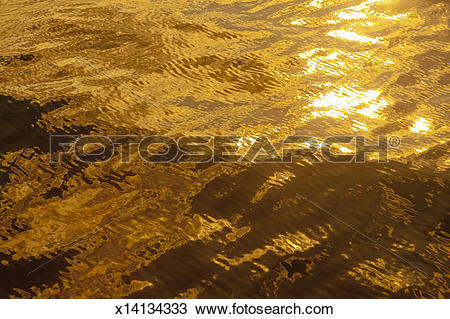 Stock Photo of Sunlight on gently rippled golden water x14134333.