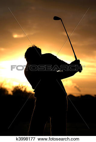 Picture of A left handed golfer practices early morning with a.