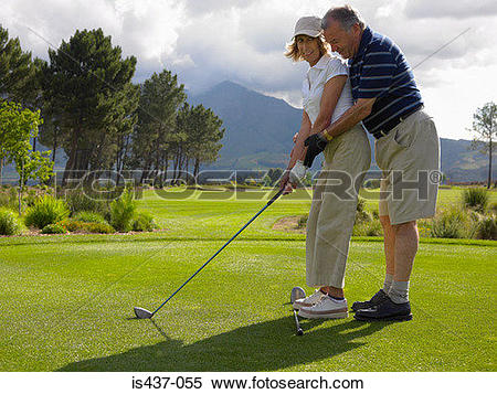 Stock Image of Man giving woman a golf lesson is437.