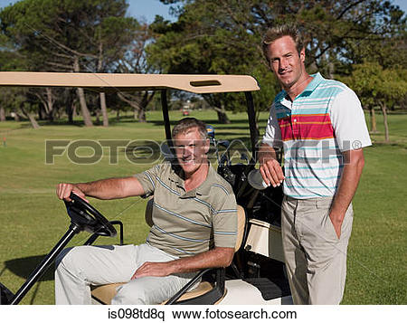 Stock Image of Two mature men in golf cart on golf course.