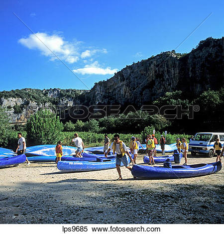 Stock Image of PEOPLE WITH CANOES ON ARDECHE RIVER BANK GORGES DE.
