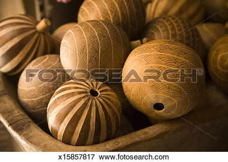Picture of Hand carved dried gourds fill a wooden bowl. x15857817.