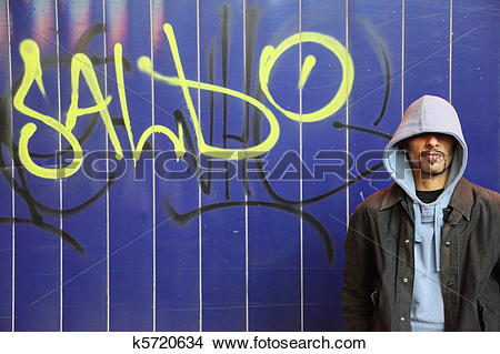 Stock Photo of one man is staying near wall with graffiti in a.