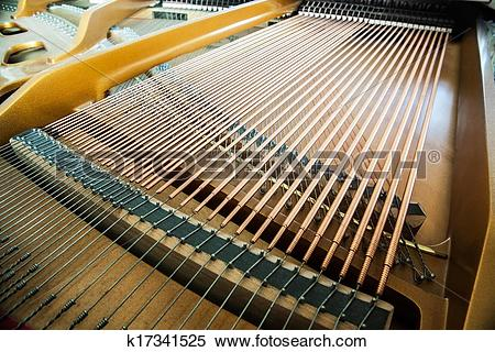 Stock Image of Closeup of grand piano showing the strings, pegs.