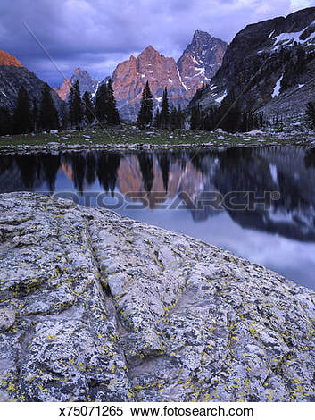 Stock Image of sunset light on grand teton peak and lake solitude.