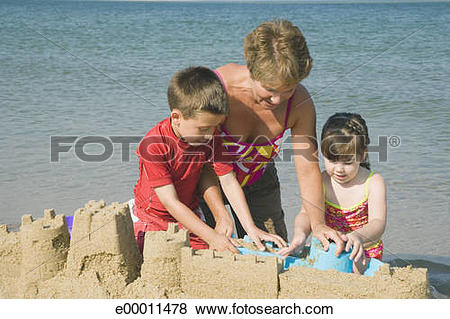 Pictures of Children building sand castle with grandmother.