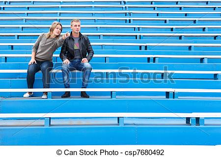 Stock Photo of Man and woman sitting on grandstand.