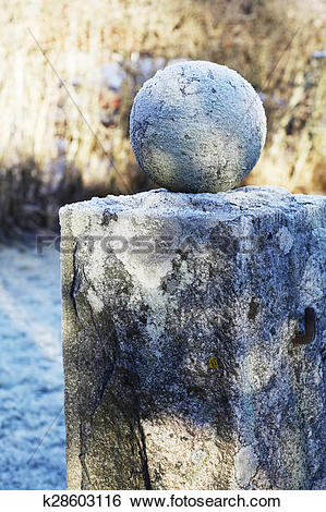 Stock Images of granite ball on a pedestal covered with frost.