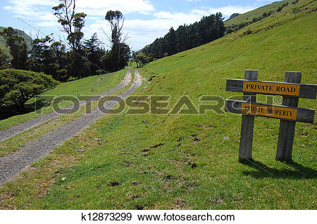 Stock Photograph of Gravel road rural area yellow sign k12873299.