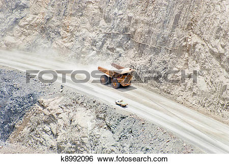 Stock Images of huge dump truck moving downhill passing normal car.