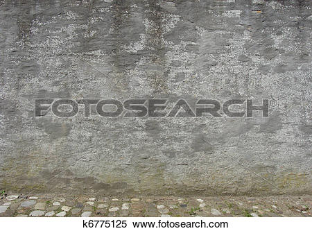 Stock Image of old worn gray concrete wall with cobble street.