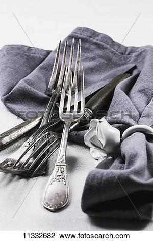 Stock Photo of Old silver cutlery with a grey napkin on a white.