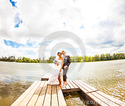 Beautiful Bride With Groom By A Lake. Kiss And Hug Stock Photo.