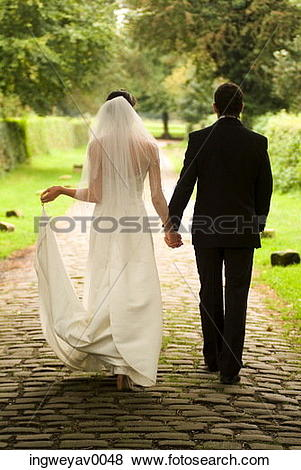 Pictures of Rear view of a young bride and groom walking in a.