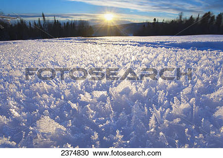 Stock Photography of Hoar frost crystals on the ground illuminated.