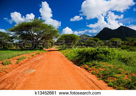 Stock Photography of Red ground road, bush with savanna. Tsavo.