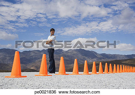 Stock Images of Man with arms crossed looking at traffic cones in.