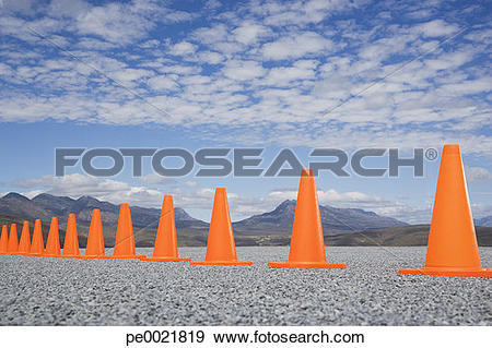 Stock Photograph of Traffic cones in line outdoors ground level.