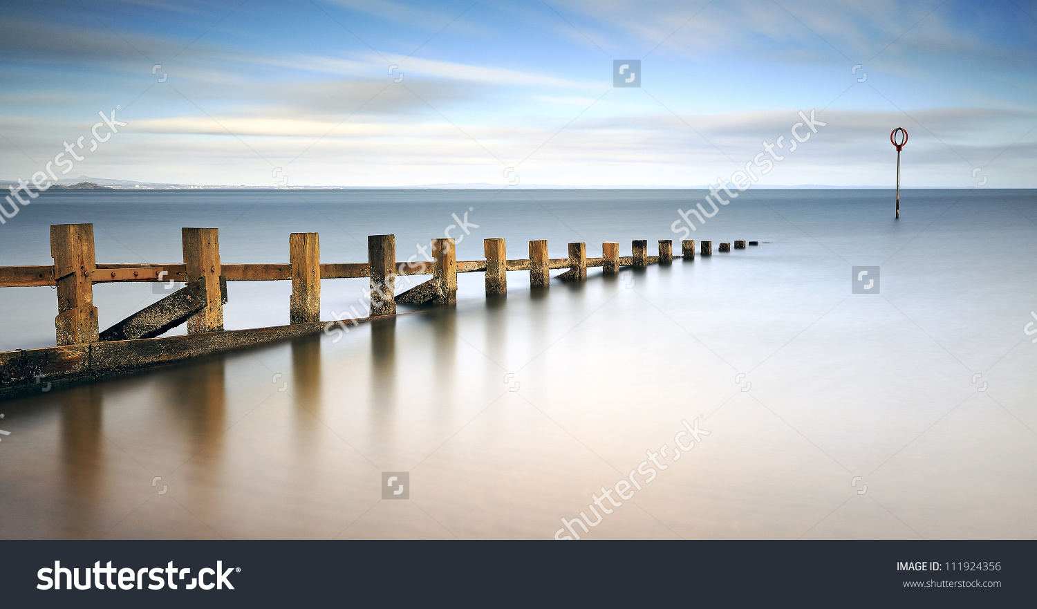 Long Exposure Of Wooden Groynes Leading In To The North Sea At.
