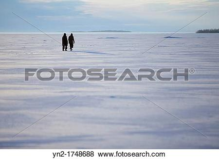 Pictures of Two women walking on sea ice. Location Gulf of Bothnia.