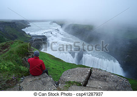 Stock Photos of Tourist looks at the big waterfall in Iceland.
