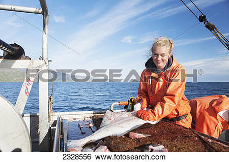 Stock Images of Young woman gutting halibut while commercial.