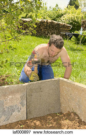 Picture of Young man fixing stone slabs for a raised bed with a.