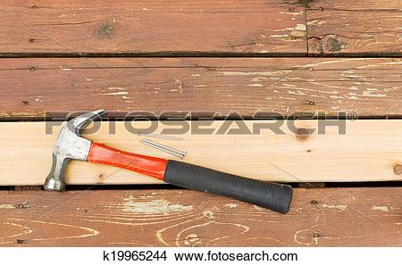 Stock Photo of Hammer and nails on top of new cedar wooden board.