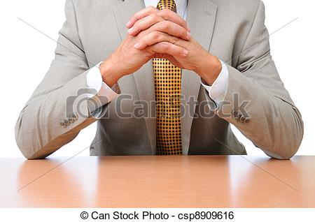 Stock Image of Businessman Elbows on Desk Hands Folded.