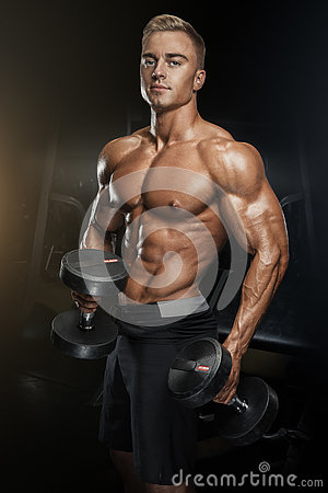 Handsome Athletic Guy Workout With Dumbbells Stock Photo.