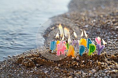 Birthday Candles Burning On A Seashore Stock Photo.