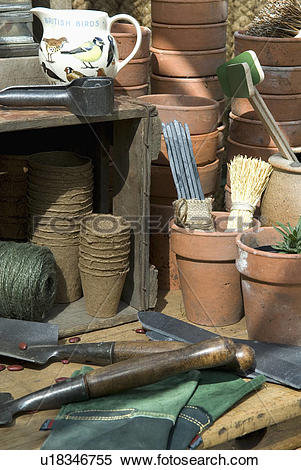 Stock Image of Greenhouse bench with terracota pots and sundry.