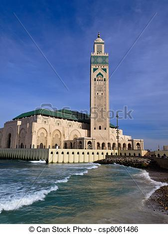 Stock Image of Ornate Hassan II Mosque against blue sky.
