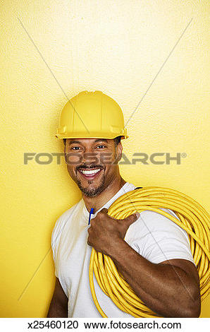 Stock Photography of Man wearing hard hat, holding extension cord.
