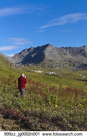Stock Photography of Male tourist photographing Hatcher Pass and.