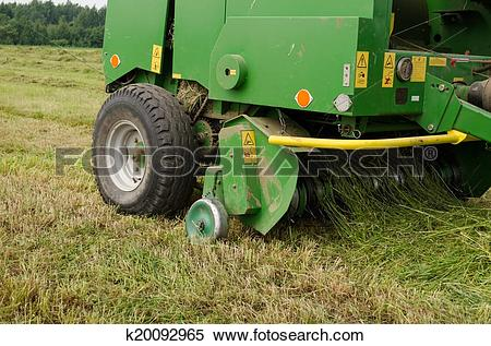 Stock Image of press machine form round fresh hay straw bale roll.