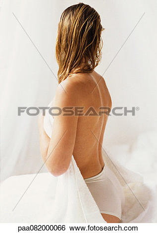 Stock Images of Partially nude woman sitting head turned away.