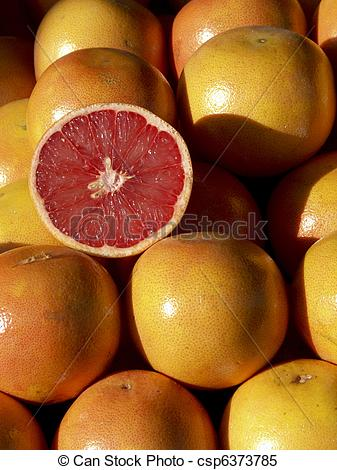 Stock Images of lots of grapefruit heaped on a market stall.