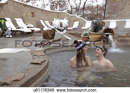 Stock Photograph of Couple in heated swimming pool during the.