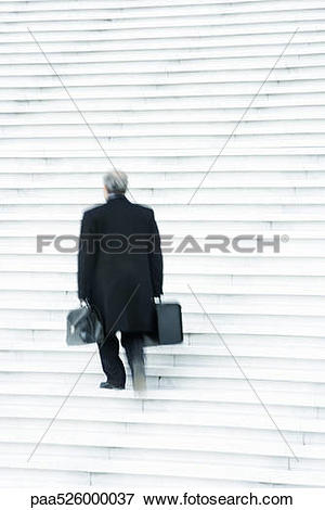 Picture of Businessman carrying two heavy bags slowly going up.