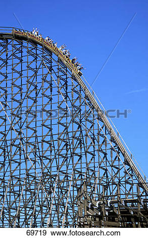 Stock Photograph of People on roller coaster in amusement park.