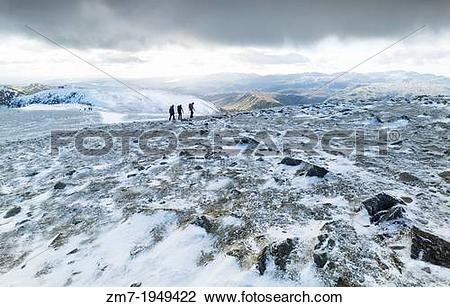 Stock Photo of Three hikers crossing the summit of Helvellyn in.